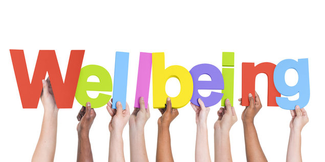 Image of multi racial hands holding letters to spell the word wellbeing